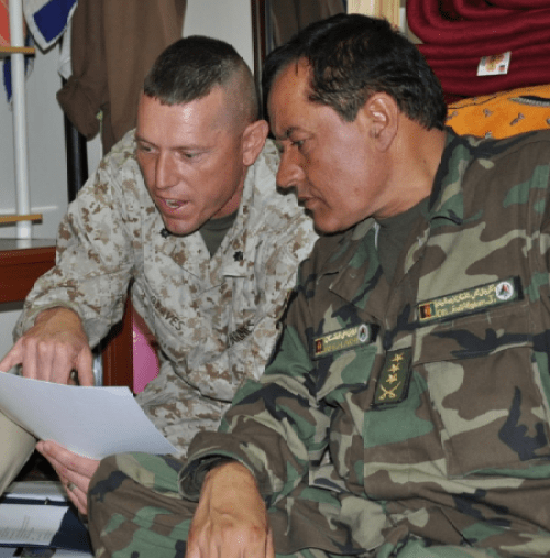 USMC Lt. Col. David Graves, a logistics advisor with the AAC-SW, interacts with an Afghan counterpart at ANA 215th Corps. (Photo by LT. Sharon Mulholland, DoD)