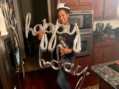 """Black woman holds """"Happy"""" and """"B-Day"""" balloons"""