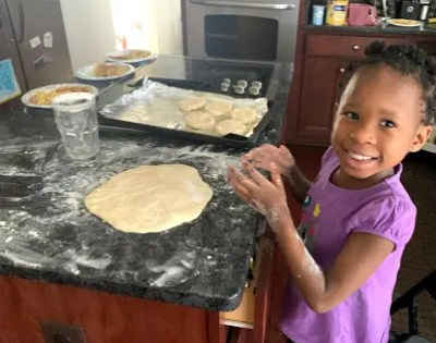 girl with flour on her hands from baking biscuits