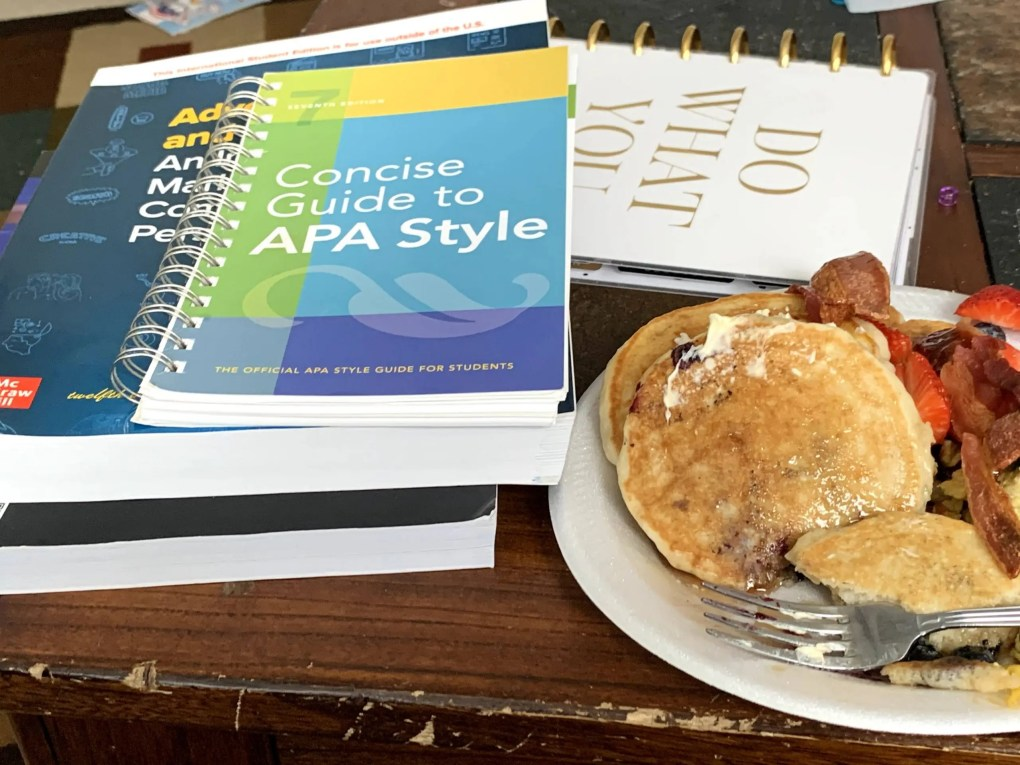 Paper Plate of pancakes and bacon beside school textbooks