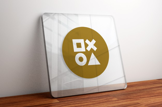 Gold logo mockup on glass on wooden table Premium Psd
