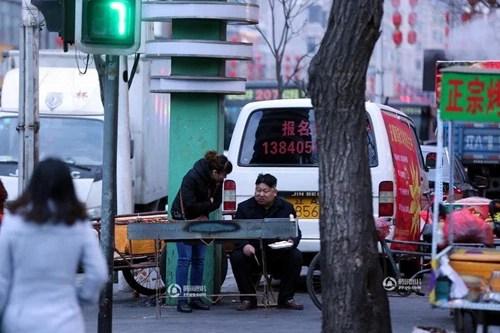 Một người khách trò chuyện với chủ quầy hàng thịt xiên nướng.