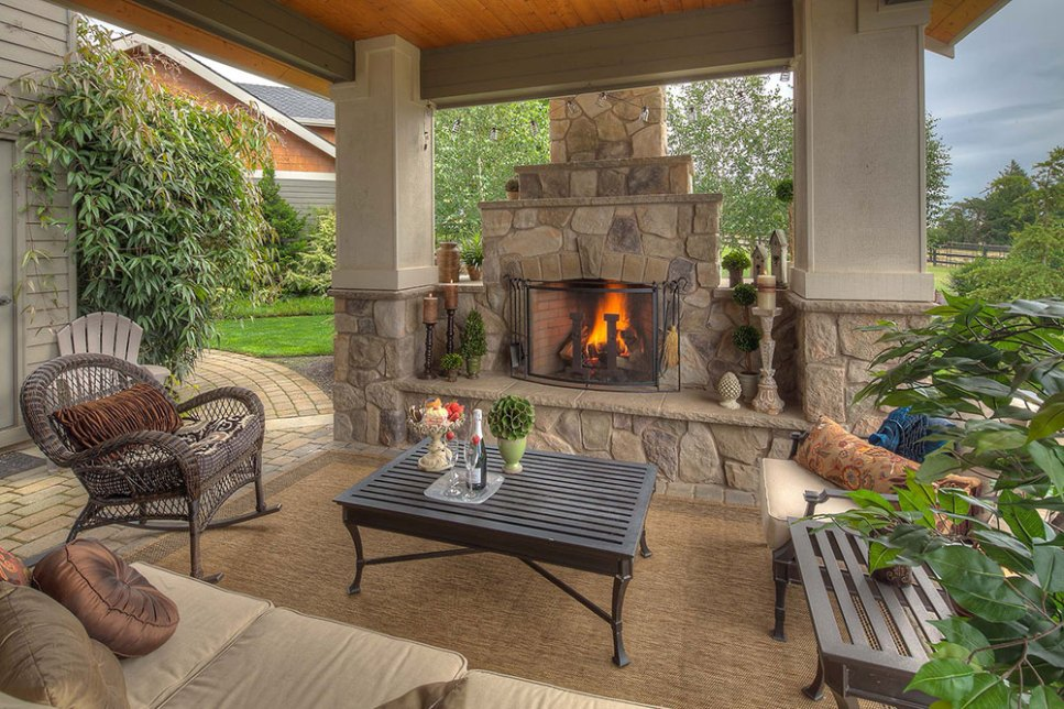 A covered patio with a stone fireplace for cozy gatherings