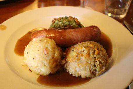 Combinaison de hutspot, boerenkool- et zuurkoolstamppot accompagnés d'une boulette ou d'une demi saucisse fumée