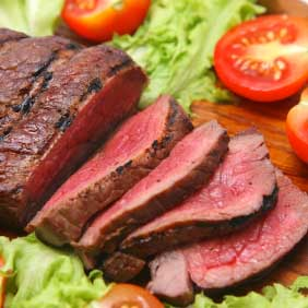 grilled red beef meat on wooden plate