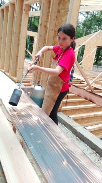 Notre fille avec un chalumeau à la main brûle du bois sur le chantier de construction.