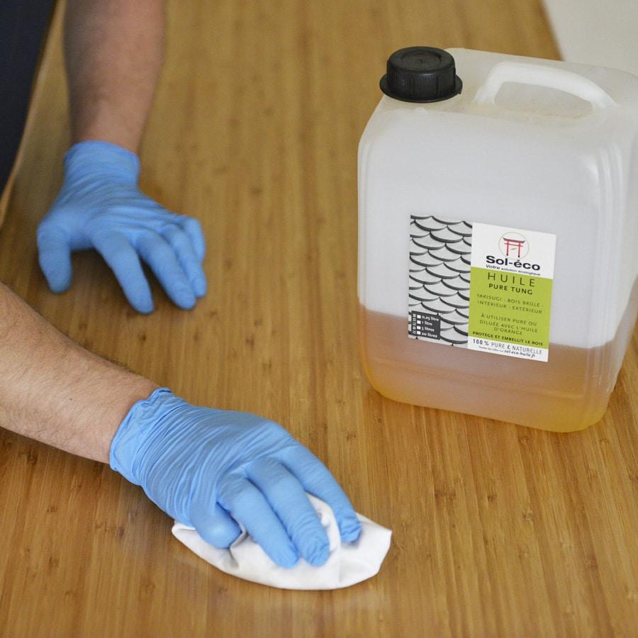 essuyage des surplus d'huile de tung à l'aide d'un chiffon