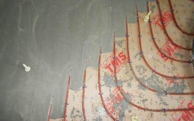 Coulage d'une chape liquide pour la réalisation d'un plancher chauffant hydraulique.