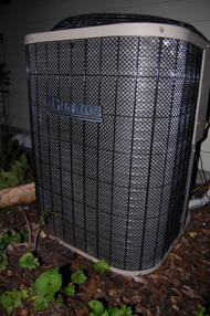 picture of central air conditioner outside a home