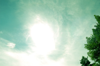 greened sky with clouds and sun
