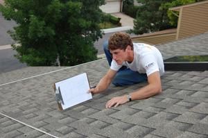 man measuring rooftop for solar installation