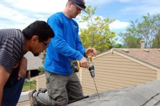 Tim (right) makes the first roof penetration with a drill with an impressively long bit at 10:50 a.m. on Day 1 as Joel (left) looks on.