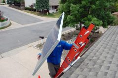 At exactly 1:05 p.m. on Day 2 Tim hoists the first solar panel onto our roof! (Each panel weighs about 35 lbs.)
