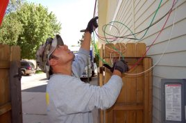 Dustin feeds the wiring from the inverter upward.