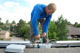 Tim works with wiring coming out of the main junction box at the top of the roof late on Day 2.