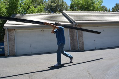 Vincent carries a solar railing to the garages to be installed on Day 1.