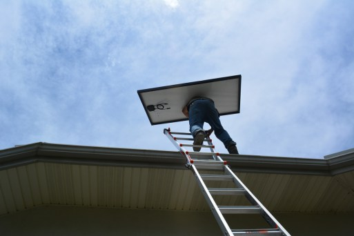 Vincent crests the ladder with a solar panel.