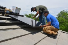 Vincent and Shane install a solar panel.