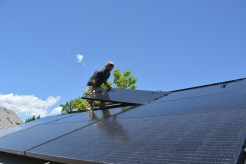 Shane lays a panel on the 20-panel array on the south roof of the HCC Common House.