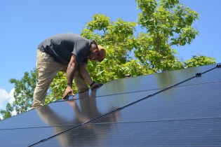 Shane lays the final solar panel of the installation at around 2:30 p.m. on June 27, 2020.