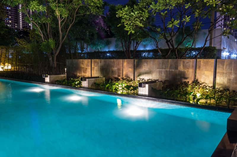 in ground pool illuminated with solar lights