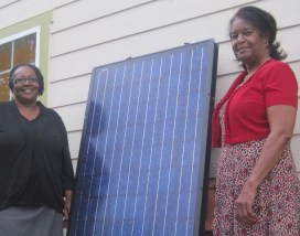 Board member Cheryl Peterson and Director of Clean Greens Farm & Market Lottie Cross with a solar panel