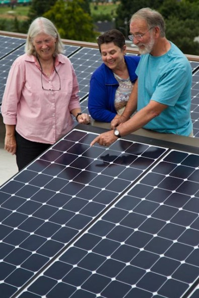 Three people looking at solar panel.