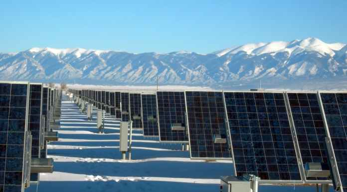 silver and black solar panels on snow covered ground