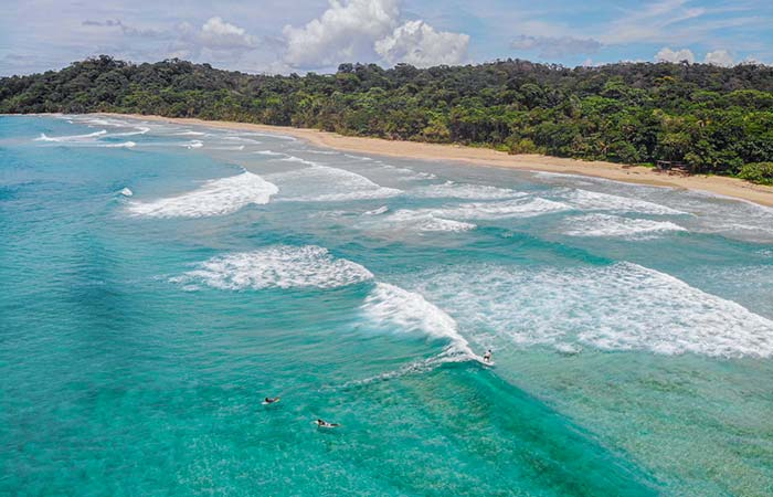 wizard beach drone surf with empty beach and jungle and clear blue water in bocas del toro panama