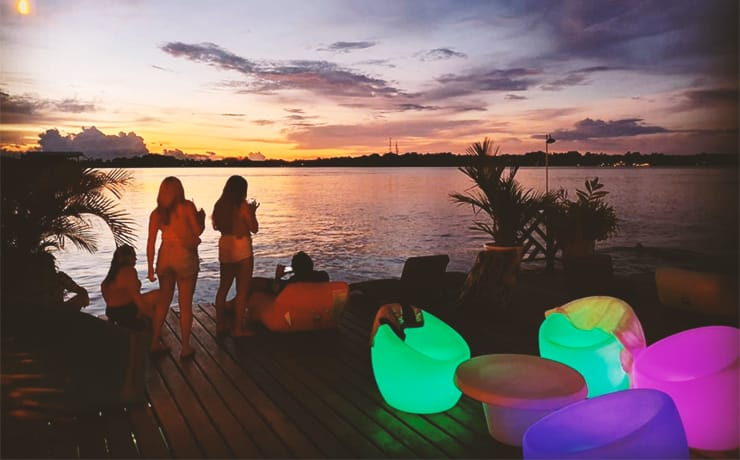 Girls stand on the deck of hostel mamallena in bocas del toro, panama, during sunset hour with neon glowing chairs.