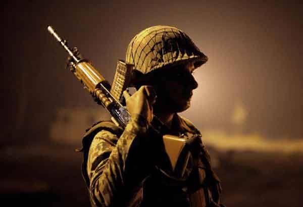 Soldier with helmet and gun on shoulder