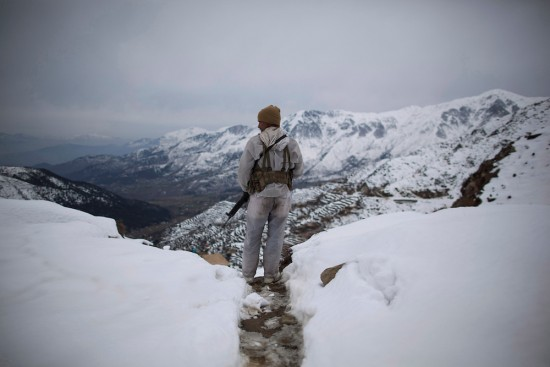 A Pakistani Army soldier with the 20th Lancers Armored Regiment, stands atop the 8000 foot mountain during a patrol near his outpost Kalpani Base in Pakistan's Dir province on the Pakistan-Afghan border, Friday, Feb 17, 2012. Kalpani is on the front line in the 10-year war against militant Islamists, a war which partners Pakistan with the United States and NATO. The partnership has been an uneasy one and at times the United States and Pakistan seem more enemies than friends. (AP Photo/Anja Niedringhaus)
