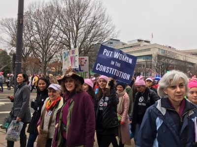 Women Lace Up Tennis Shoes To March
