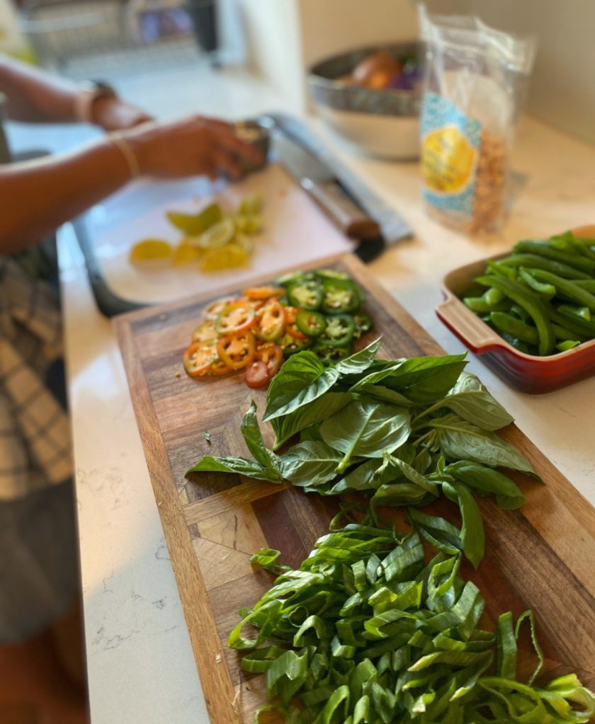 A cutting board of jalapeno peppers basil, and lime or mise en place to help you cook like a chef at home.