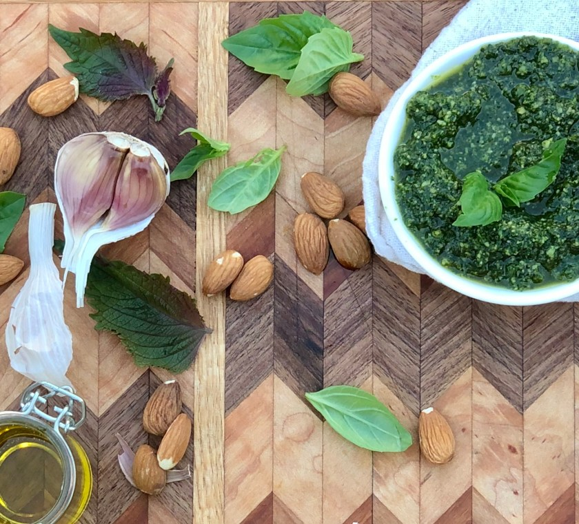 A bowl of pesto sitting on a cutting board surrounded by garlic, almonds, basil, shiso and olive oil.