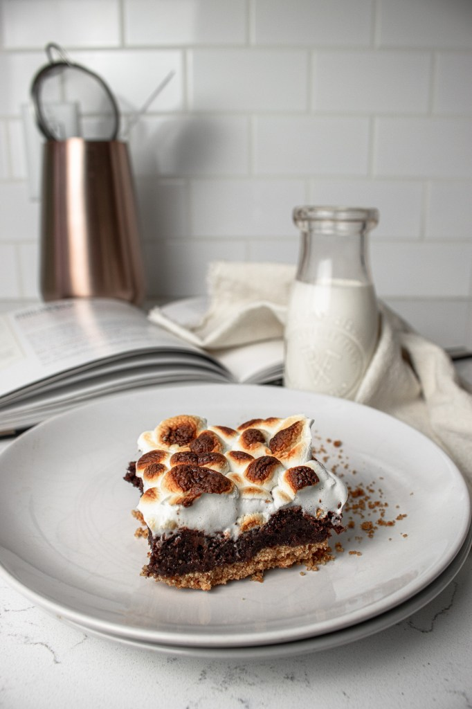one s'mores brownie on a plate with milk