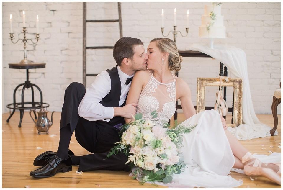 Bride and groom kissing sittin on the floor in South Dakota.