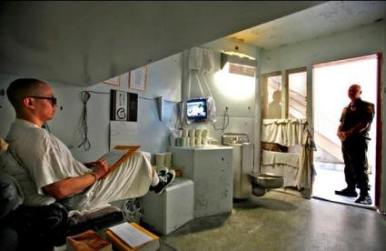 A prisoner watches TV wile writing a letter