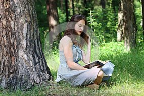 beautiful-girl-dress-sitting-under-tree-grass-reading-book-52635232