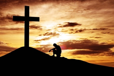 15193306 - a man making a confession to the cross, shot under dawn sky