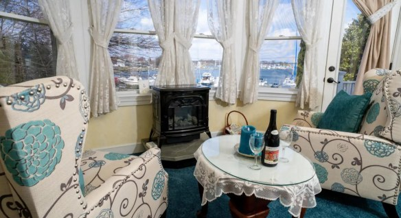 Two upholstered arm chairs with a bold teal and brown flower pattern sitting next to a small table with glass top near a fireplace next to large windows with a view of the marina