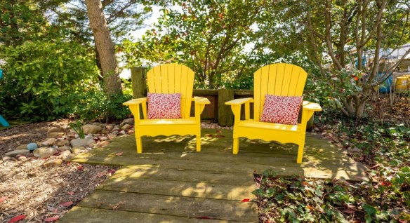 Two bright yellow adirondack chairs each with a red and white floral patterned pillow surrounded by green shrubs and trees