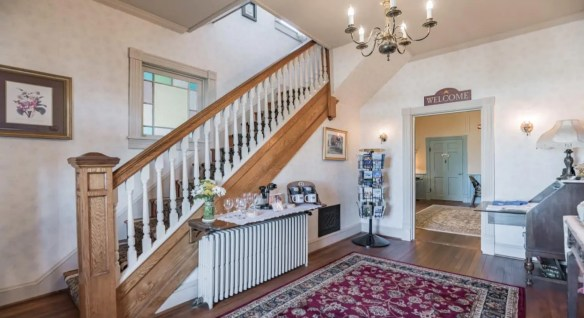 Entry area with light colored wallpaper, hardwood floors, large area rug, and wooden staircase with white spindles leading up to the second floor