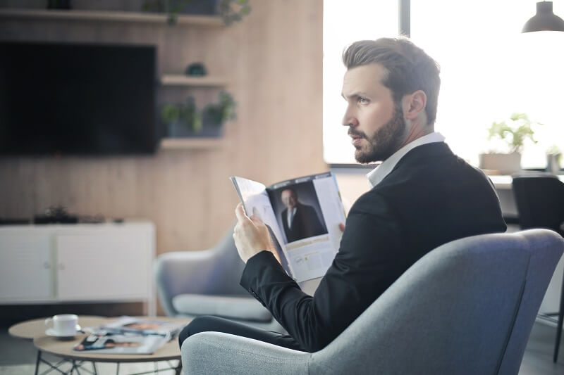 man-sitting-on-chair-holding-a-magazine-3480329