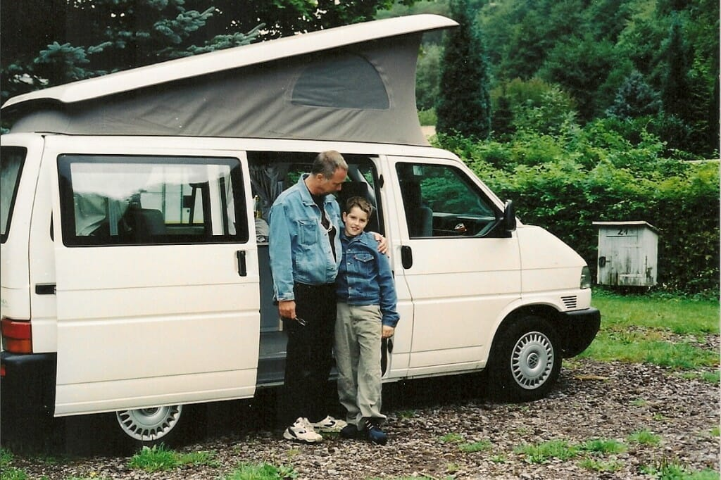 white, vw pop up camper with father and son standing in front