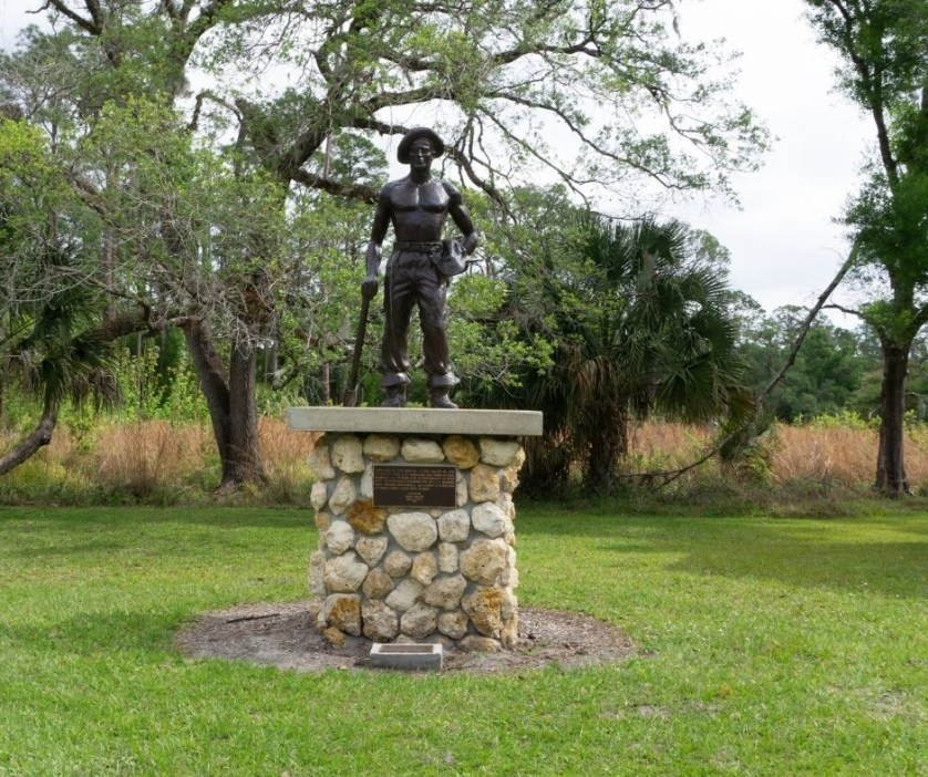 """A statue next to the CCC Museum. It reads, """"dedicated to the memory of Emil Billitz Sr. and countless other CCC enrollees who were injured, disabled or lost their lives in performance of their duty. We especially remember the 228 CCC members who perished September 2, 1935 during a hurricane at three camps, Upper Keys, Florida. Donated by Henry Billitz and N.A.C.C.C.A., 1997"""""""