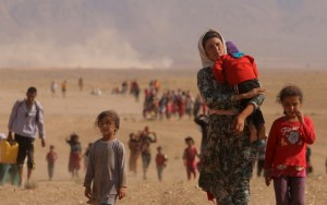Displaced people from the minority Yazidi sect, fleeing violence from forces loyal to the Islamic State in Sinjar town, walk towards the Syrian border