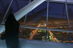A Saudi woman looks out over Riyadh from the 99th floor of the Kingdom Tower.