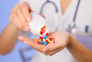 Woman pouring chronic diarrhea medication pills