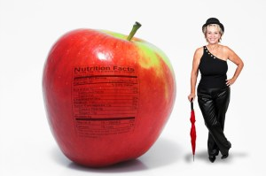 Sexy middle aged woman with cane and derby, standing by a giant apple.